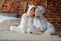 Dos niños en los pijamas que se sientan en los regalos de la Navidad de la cama que esperan para Foto de archivo
