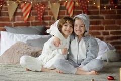 Dos niños en los pijamas que se sientan en los regalos de la Navidad de la cama que esperan para Fotos de archivo