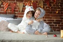 Dos niños en los pijamas que se sientan en los regalos de la Navidad de la cama que esperan para Fotos de archivo libres de regalías