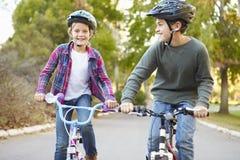 Dos niños en paseo del ciclo en campo Imagenes de archivo