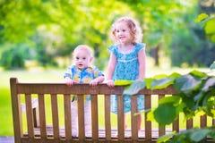 Dos niños en un banco de parque Foto de archivo libre de regalías