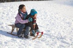 Dos niños en un trineo que se divierte Fotos de archivo libres de regalías