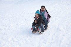 Dos niños en un trineo que se divierte Imagen de archivo libre de regalías