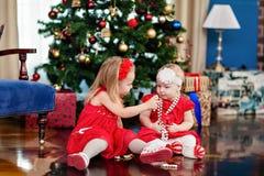 Dos niños en vestidos rojos en el fondo del Christma Fotos de archivo libres de regalías