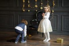 Dos niños encantadores disfrutan a los regalos de la Navidad Fotos de archivo libres de regalías