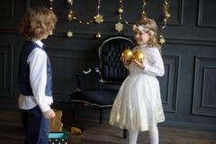 Dos niños encantadores disfrutan a los regalos de la Navidad Fotografía de archivo