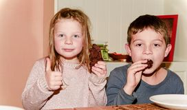 Dos niños están comiendo las galletas marrones que la muchacha está dando thum para arriba Concepto divertido y de los niños Añad foto de archivo libre de regalías