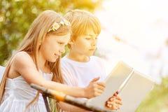 Dos niños están jugando con la tableta en Internet Imagen de archivo libre de regalías