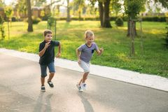 Dos niños están jugando en el parque Dos muchachos hermosos en camisetas y pantalones cortos tienen sonrisa de la diversión Comen Foto de archivo