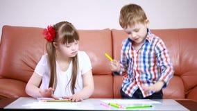 Dos niños felices adorables que dibujan con los creyones en el playschool muchacha con Síndrome de Down rehabilitación del discap metrajes