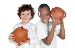 Dos niños felices con ahorros del moneybox imagenes de archivo