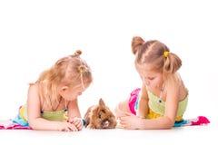 Dos niños felices con el conejito y los huevos de pascua. Pascua feliz Imagen de archivo