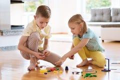 Dos niños felices curiosos que juegan con el juego Foto de archivo