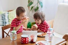 Dos niños felices, dos hermanos, desayunando sano que sienta a Imagen de archivo libre de regalías