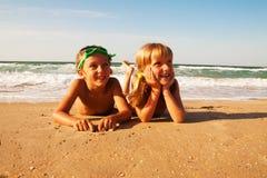 Dos niños felices en la playa, mar en fondo. Foto de archivo
