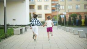 Dos niños felices funcionados con juntas llevando a cabo las manos Su onda del pelo rubio hacia fuera en el viento almacen de video