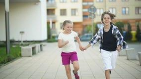 Dos niños felices funcionados con juntas llevando a cabo las manos Su onda del pelo rubio hacia fuera en el viento almacen de metraje de vídeo