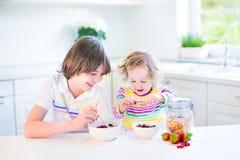 Dos niños felices que comen fruta para el jugo de consumición del desayuno Fotos de archivo libres de regalías