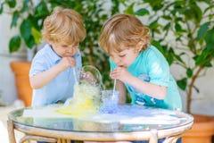 Dos niños felices que hacen el experimento con las burbujas coloridas Fotografía de archivo libre de regalías