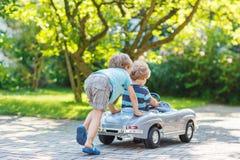 Dos niños felices que juegan con el coche del juguete Foto de archivo