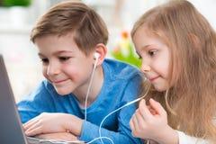 Dos niños felices que juegan con el ordenador portátil y la música que escucha con foto de archivo