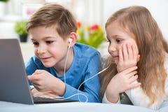 Dos niños felices que juegan con el ordenador portátil y la música que escucha con imagen de archivo