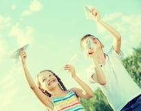 Dos niños felices que juegan con los aviones de papel simples Imágenes de archivo libres de regalías