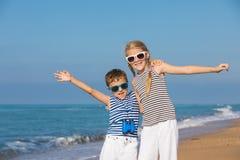 Dos niños felices que juegan en la playa en el tiempo del día Foto de archivo