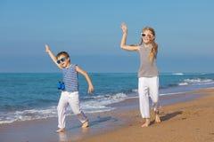 Dos niños felices que juegan en la playa en el tiempo del día Imagen de archivo libre de regalías