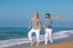 Dos niños felices que juegan en la playa en el tiempo del día Fotografía de archivo libre de regalías