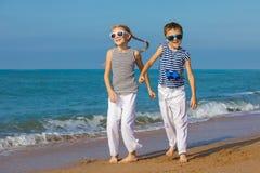 Dos niños felices que juegan en la playa en el tiempo del día Fotografía de archivo