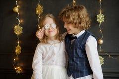 Dos niños festivamente vestidos fotografiados para la tarjeta de Navidad Foto de archivo