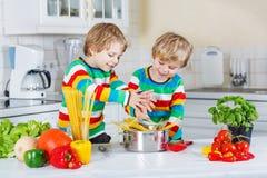 Dos niños gemelos divertidos que cocinan la comida italiana con spahetti Imagenes de archivo