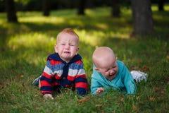 Dos niños gritadores que mienten en hierba Imagen de archivo libre de regalías
