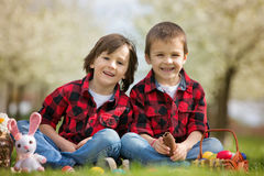 Dos niños, hermanos del muchacho, comiendo conejitos del chocolate y teniéndolos Fotografía de archivo