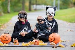 Dos niños, hermanos del muchacho en el parque con los disfraces de Halloween fotos de archivo libres de regalías