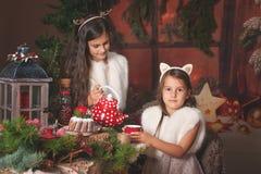 Dos niños hermosos, hermanas, teniendo la fiesta de Navidad en la cabaña de madera de la familia, atmósfera acogedora de la Navid Fotos de archivo libres de regalías