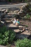 Dos niños jovenes descansan mientras que exploran en un jardín público Imagen de archivo