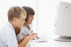 Dos niños jovenes en Ministerio del Interior con el ordenador Fotos de archivo