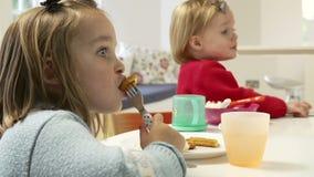 Dos niños jovenes que comen la comida en casa almacen de metraje de vídeo