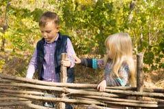 Dos niños jovenes que juegan en una cerca de madera Foto de archivo