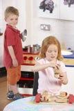 Dos niños jovenes que juegan junto en Montessori/ Fotografía de archivo libre de regalías