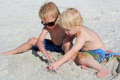 Dos niños jovenes que juegan los juguetes en la arena en la playa Foto de archivo