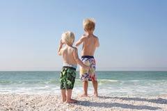 Dos niños jovenes que miran hacia fuera sobre el océano en la playa Fotos de archivo libres de regalías