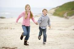 Dos niños jovenes que se ejecutan en la playa Imagen de archivo libre de regalías