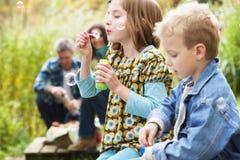 Dos niños jovenes que soplan el outisde de las burbujas Fotografía de archivo libre de regalías