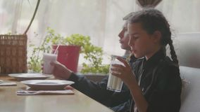 Dos niños lindos que beben los batidos de leche o los alimentos de preparación rápida condimentados del café video de la cámara l almacen de metraje de vídeo