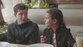Dos niños lindos que beben los batidos de leche o los alimentos de preparación rápida condimentados del café video de la cámara l metrajes