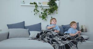 Dos niños miran a un programa de televisión emocionante en la TV Dos hermanos están viendo la TV almacen de metraje de vídeo