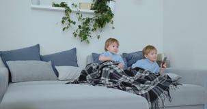 Dos niños miran a un programa de televisión emocionante en la TV Dos hermanos están viendo la TV almacen de video